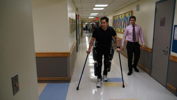 Robert Woo (L) walks using the ReWalk